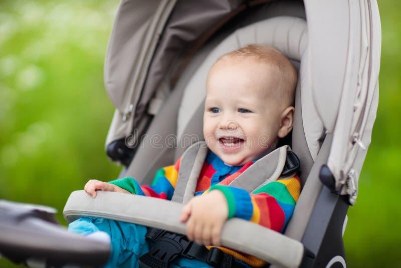 Babyjongen in warme kleurrijke gebreide jasjezitting in moderne wandelwagen op een gang in een park Kind in met fouten Weinig jon stock afbeeldingen