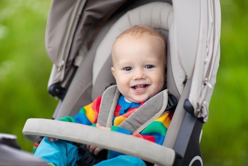 Babyjongen in warme kleurrijke gebreide jasjezitting in moderne wandelwagen op een gang in een park Kind in met fouten Weinig jon royalty-vrije stock afbeelding