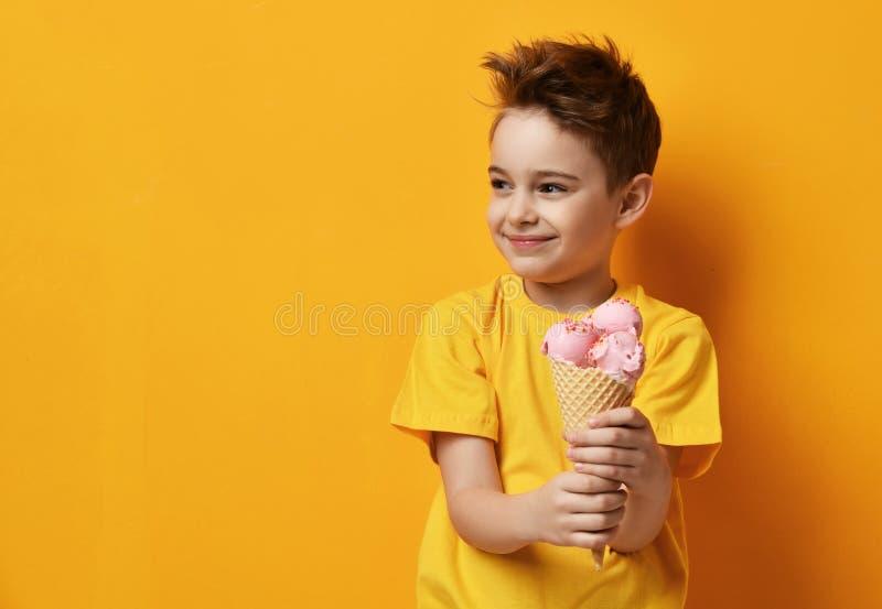 Babykind, das Erdbeereis im glücklichen schreienden Lachen des Waffelkegels auf gelbem Hintergrund isst lizenzfreie stockfotografie