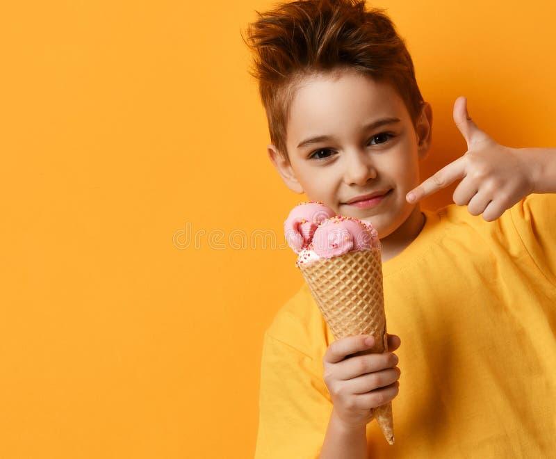 Babykind, das Erdbeereis im glücklichen schreienden Lachen des Waffelkegels auf gelbem Hintergrund isst lizenzfreie stockbilder