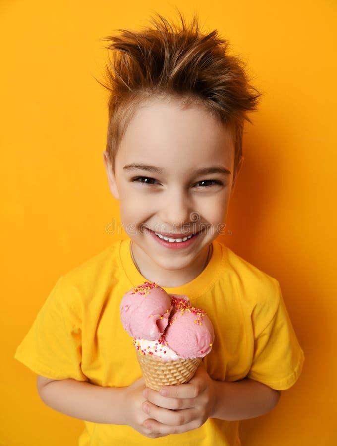 Babykind, das Erdbeereis im glücklichen schreienden Lachen des Waffelkegels auf gelbem Hintergrund isst stockbild