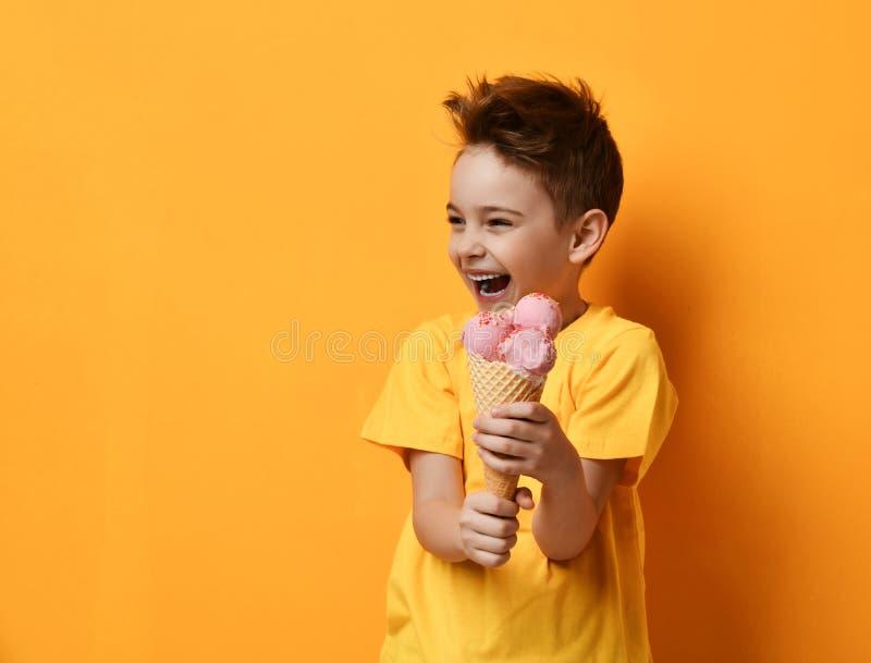 Babykind, das Erdbeereis im glücklichen schreienden Lachen des Waffelkegels auf gelbem Hintergrund isst stockfotos