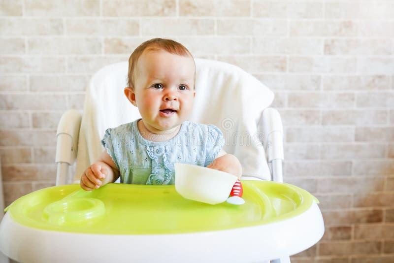 Babykind die met lepel in zonnige keuken eten Portret van gelukkig jong geitje als hoge voorzitter De ruimte van het exemplaar royalty-vrije stock fotografie