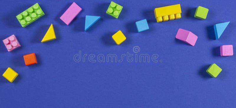 Babykind spielt Hintergrund Bunte Plastikbaublöcke und hölzerne Würfel auf blauem Hintergrund stockfoto