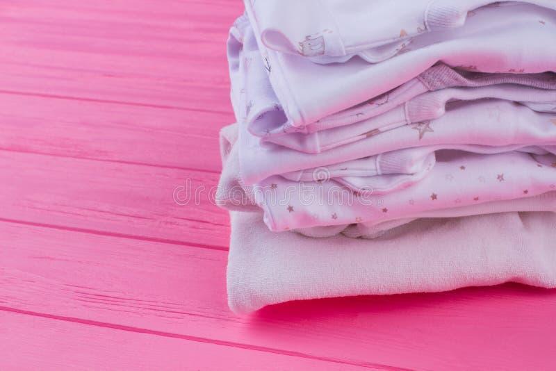 Babykleidung auf rosa Holz stockbilder