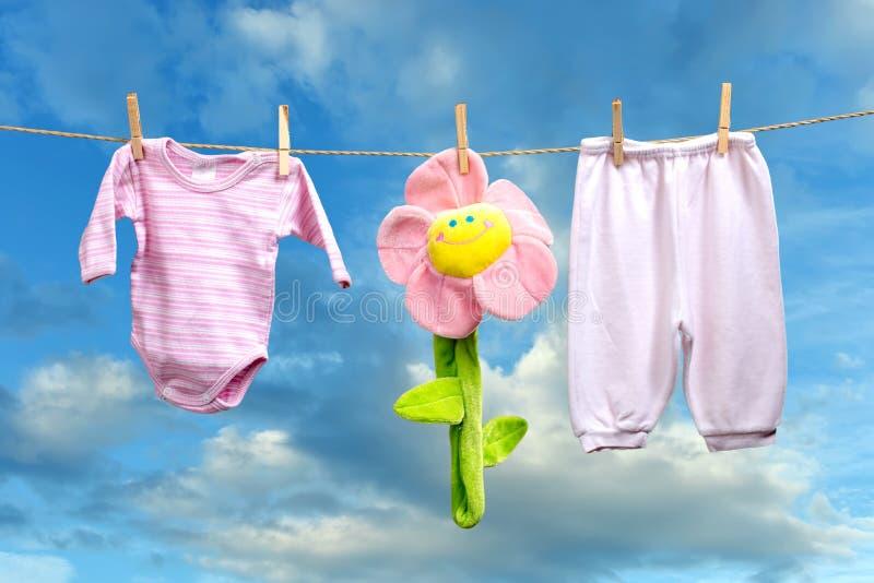 Babykleidung mit Blume auf der Wäscheleine lizenzfreie stockfotos