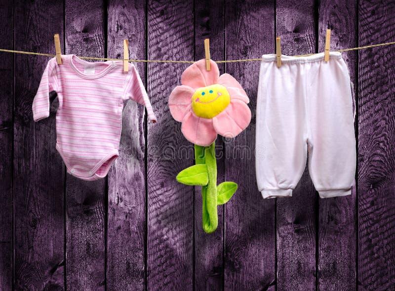 Babykleidung und eine Blume auf einer Wäscheleine lizenzfreies stockfoto