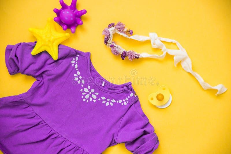 Babykleidung und -notwendigkeiten auf hellem Hintergrund stockfotografie