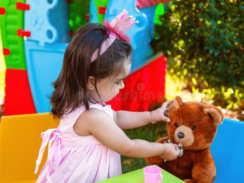Babykleinkindmädchen, das Teeparty in der im Freien einzieht ihren besten Freund Teddy Bear mit der Süßigkeit gummiartig spielt lizenzfreie stockfotografie