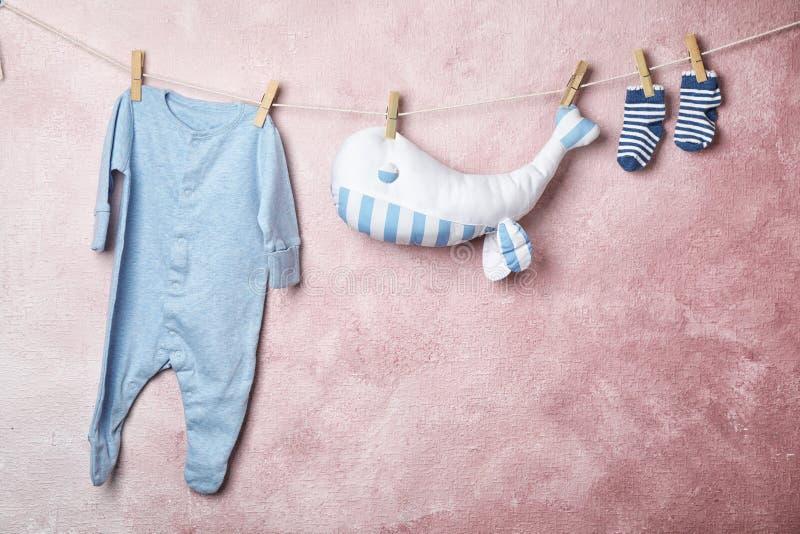 Babykleren en stuk speelgoed het hangen op kabel stock foto's