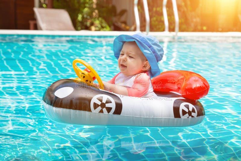 Babyliebe zu schwimmen Sommerferien in Meer Ein kleines Mädchen weniger als einjährig fährt ein aufblasbares Boot in Form a stockbild
