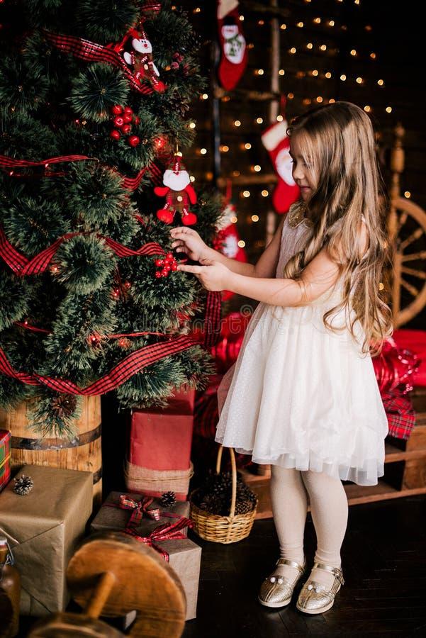 Babymeisje 4-5 éénjarigen die in ruimte over Kerstmisboom stellen met decoratie het bekijken camera Vrolijke Kerstmis Het dragen  royalty-vrije stock foto's