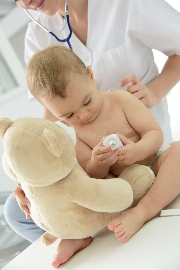 Babymeisje bij arts die een controle krijgen stock afbeeldingen