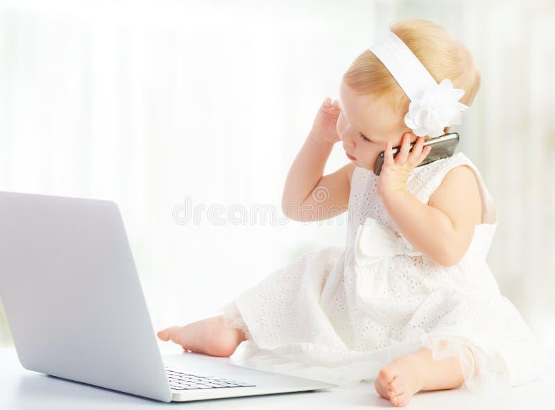 Babymeisje bij laptop computer, mobiele telefoon royalty-vrije stock afbeelding