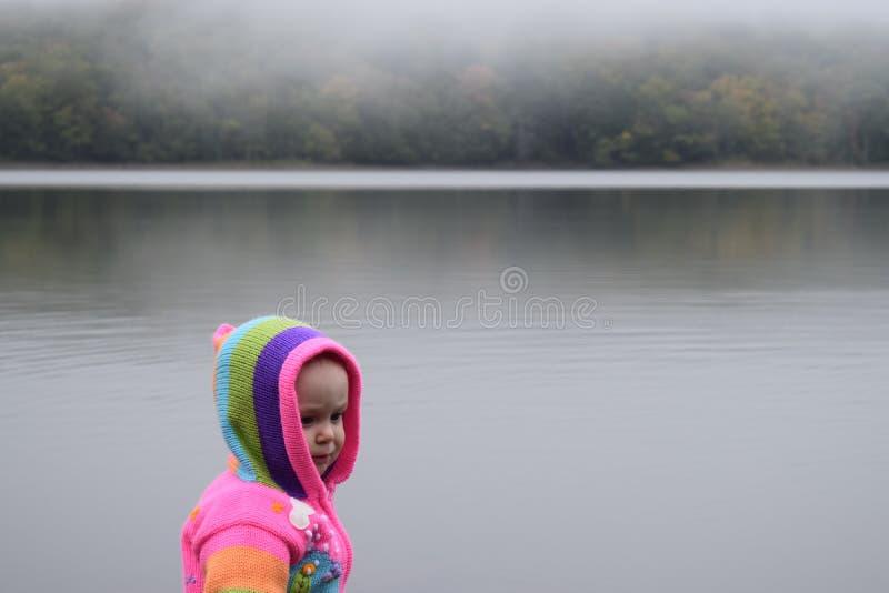Babymeisje bij mistig meer royalty-vrije stock afbeelding