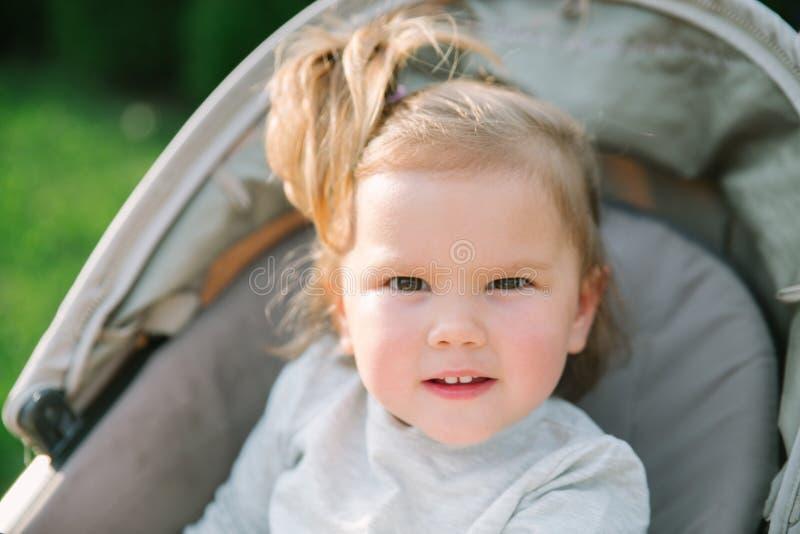 Babymeisje buiten het zitten in een wandelwagen stock afbeeldingen