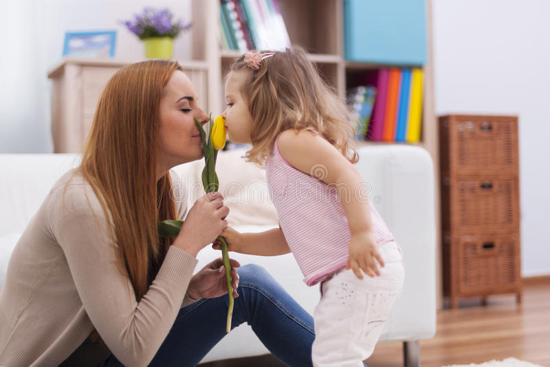 Babymeisje die bloem geven aan haar moeder stock foto's