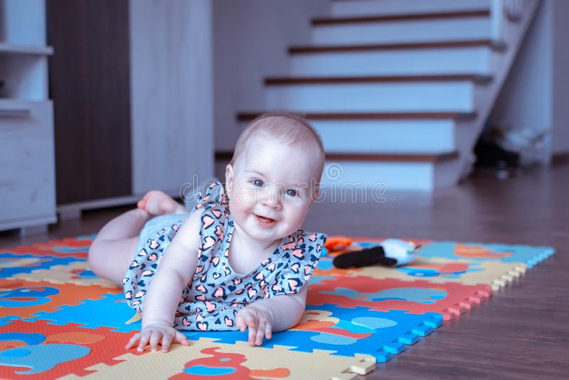 Babymeisje die buiktijd op kleurrijke spelmat doen stock fotografie