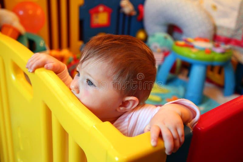 Babymeisje die in een box denken stock foto