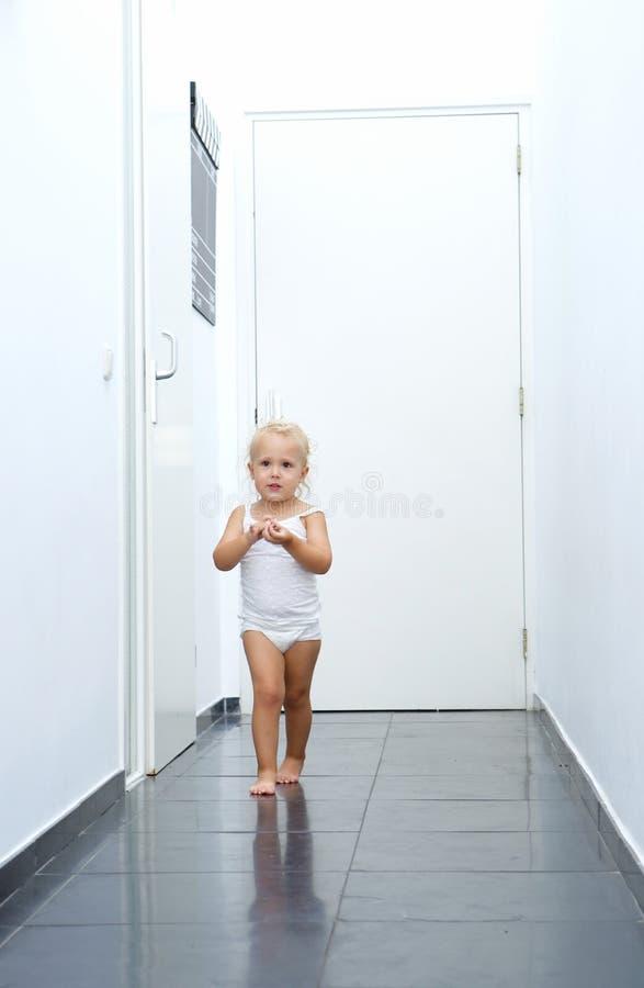 Babymeisje die in gang thuis lopen stock afbeeldingen