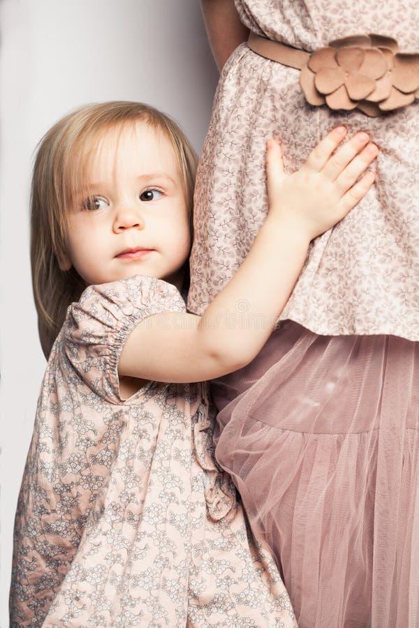Babymeisje die haar moederrok houden Kinderjarenconcept royalty-vrije stock fotografie