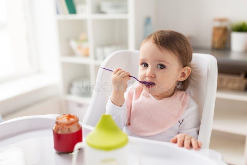 Babymeisje die met lepel puree van kruik thuis eten stock foto