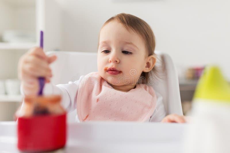 Babymeisje die met lepel puree van kruik thuis eten stock afbeeldingen