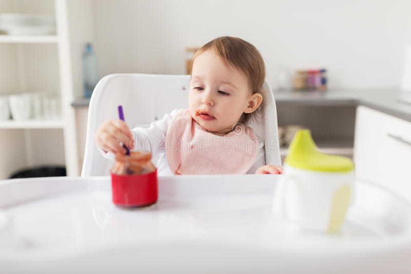 Babymeisje die met lepel puree van kruik thuis eten royalty-vrije stock foto's