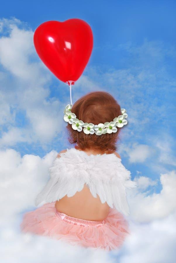 Babymeisje die met vleugels op wolk met ballon zitten stock afbeelding