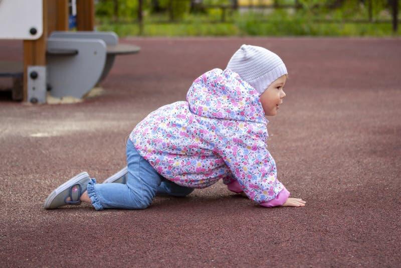Babymeisje die op alle fours op de speelplaats kruipen Een kind in warme jeans kleedt de windjekker van het hoedenjasje de gangen royalty-vrije stock foto