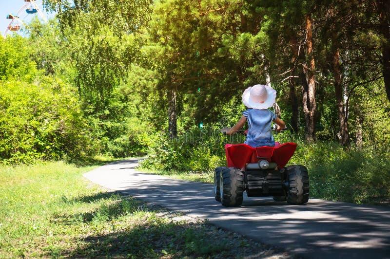 Babymeisje die op een rode ATV in een groen Park berijden stock foto's