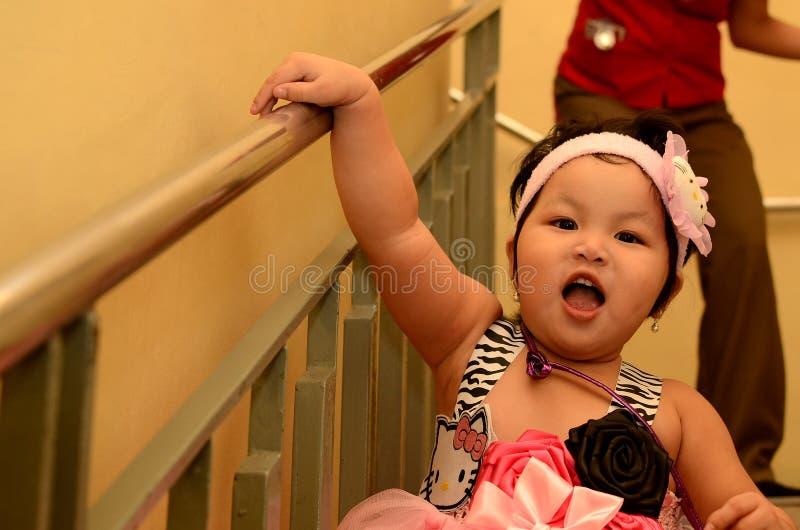 Babymeisje die pret hebben bij treden die door kelner in een viering van de verjaardagspartij worden achtervolgd royalty-vrije stock afbeeldingen