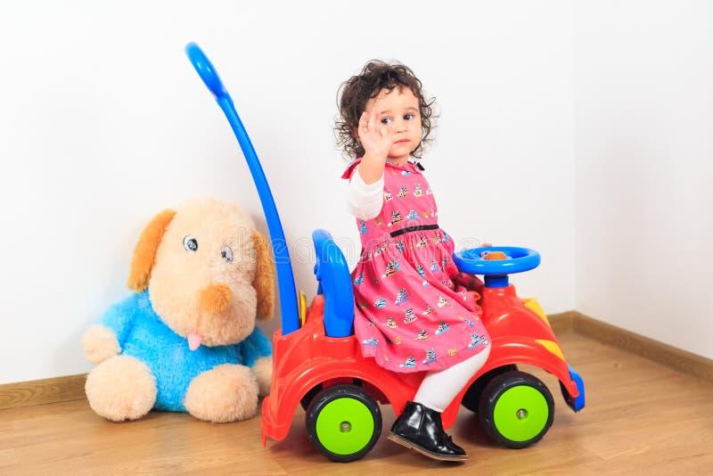 Babymeisje die vaarwel op een stuk speelgoed auto golven stock afbeeldingen