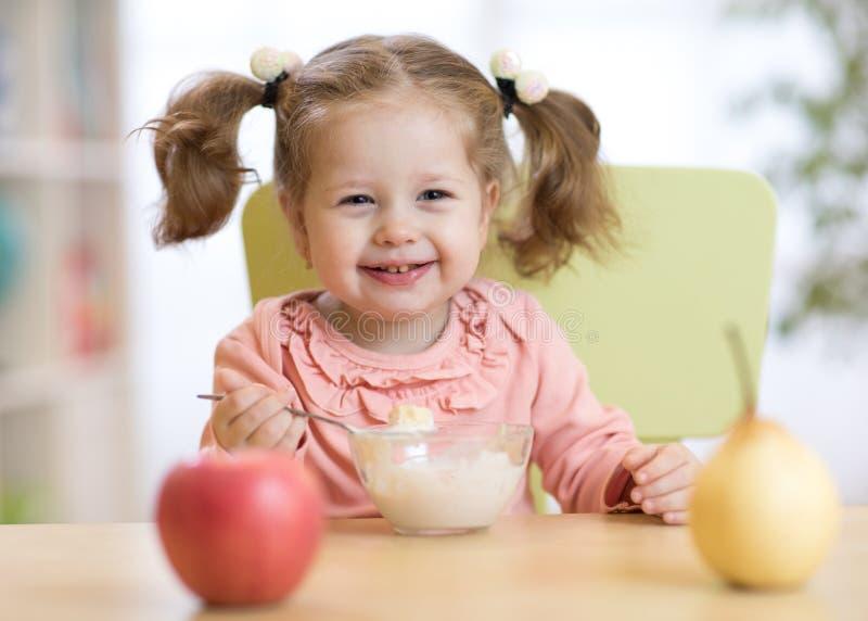 Babymeisje die vruchten thuis eten stock foto