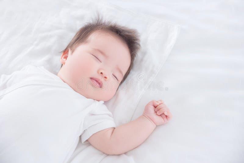 Babymeisje die witte doekslaap op wit bed dragen royalty-vrije stock foto's