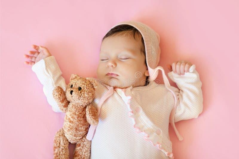 Babymeisje die in witte hoed en roze pyjama's teddybeerslaap in zijn bloedsomloop op een deken koesteren royalty-vrije stock fotografie