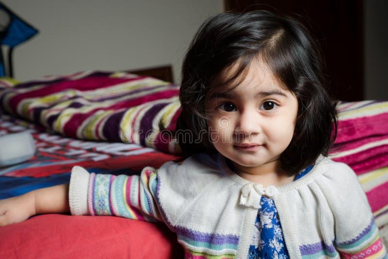 Babymeisje die zich met bed bevinden stock foto