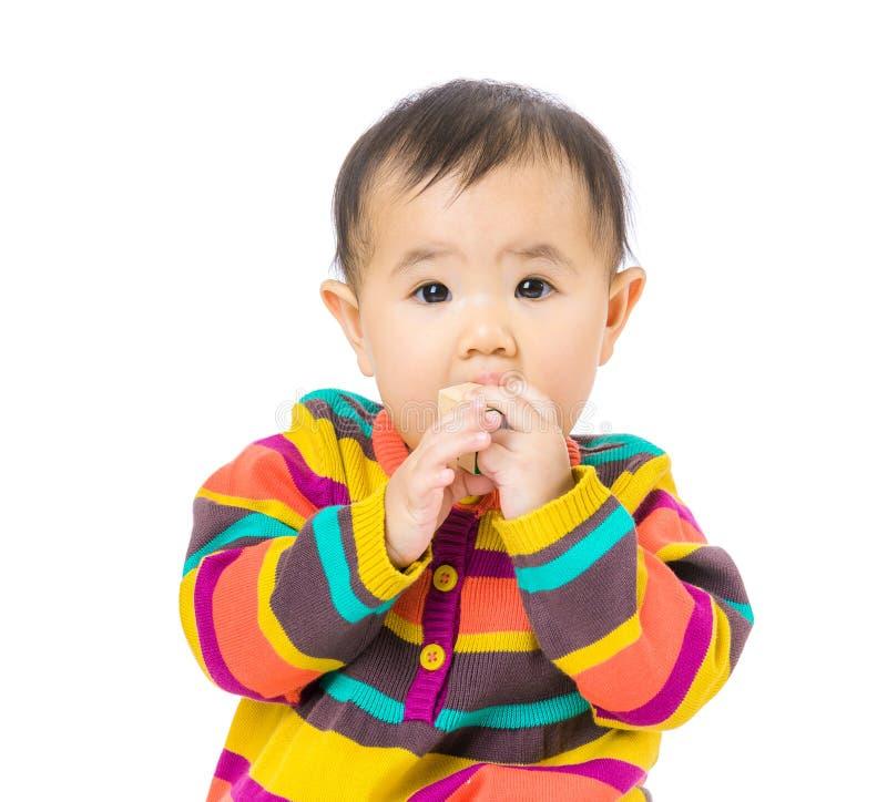 Babymeisje gezet stuk speelgoed blok in mond stock foto