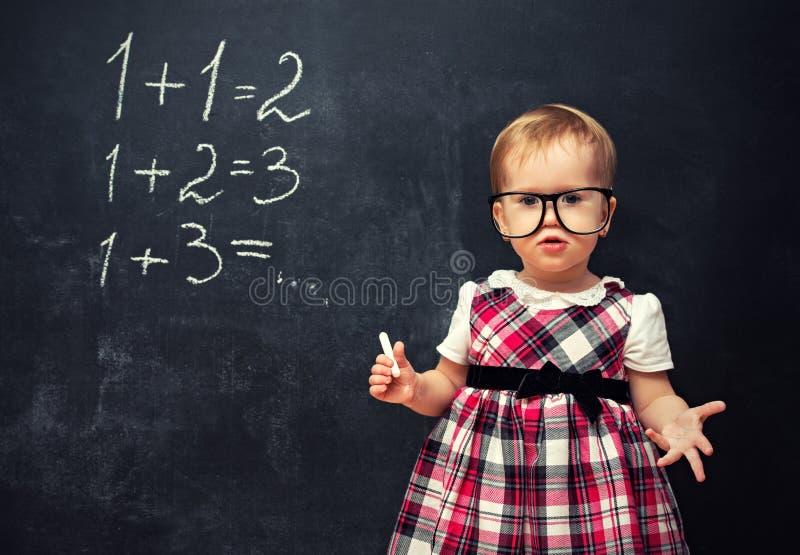 Babymeisje in glazen en krijt bij een schoolraad met arithmeti stock fotografie