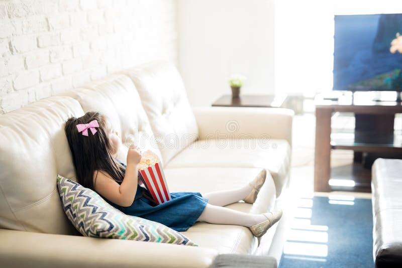 Babymeisje het letten op beeldverhaalfilm in woonkamer stock afbeeldingen