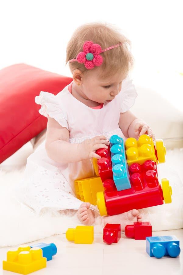 Babymeisje het spelen met bakstenen stock foto