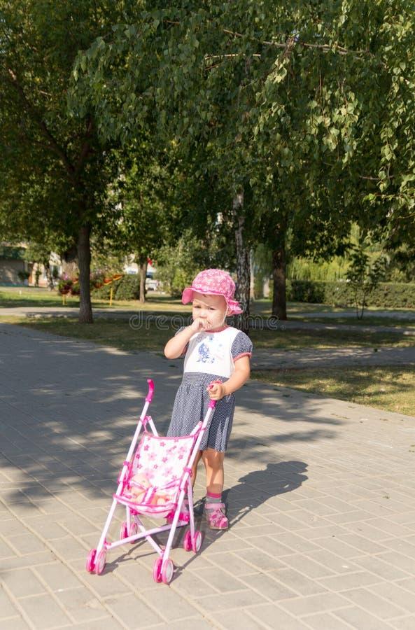 Babymeisje het spelen met een babywandelwagen stock fotografie