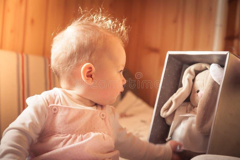 Babymeisje het spelen met pluchekonijn als gift wordt ontvangen die royalty-vrije stock foto