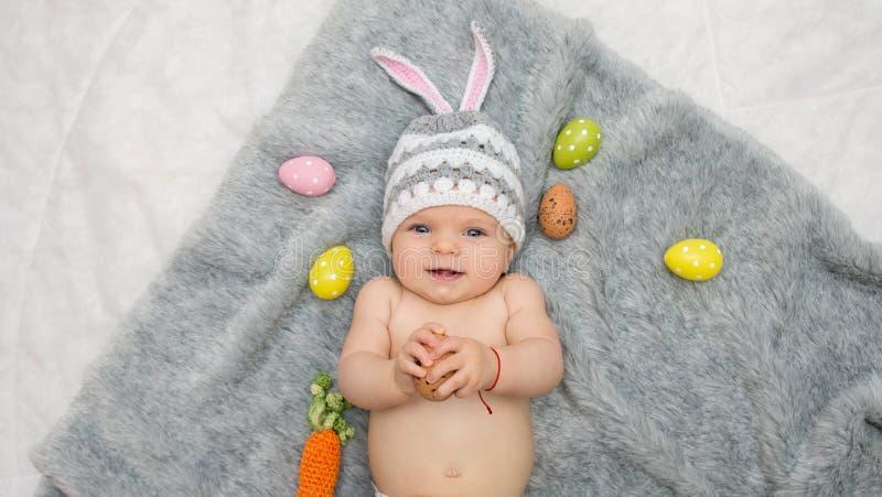 Babymeisje in konijntjeshoed die op grijze deken met multicolored paaseieren liggen stock foto's