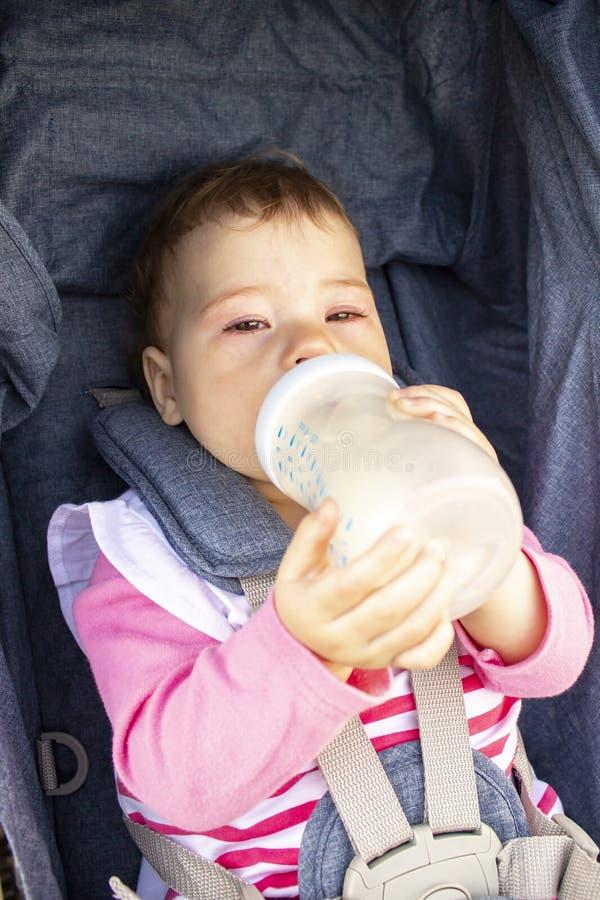 Babymeisje 9 maanden die van een zitting van de melkfles in een wandelwagen eten, zachte nadruk Een klein kind drinkt onafhankeli royalty-vrije stock afbeelding