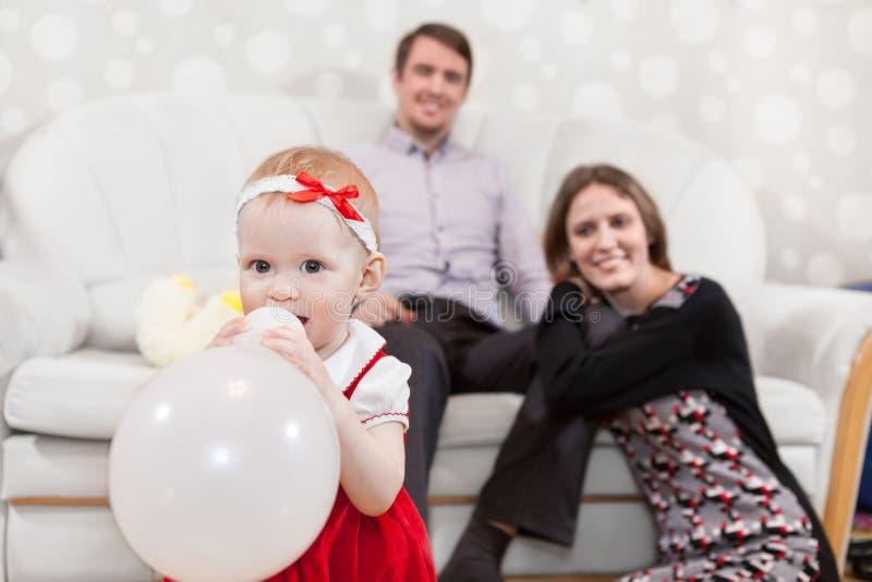 Babymeisje met ballon en vader en moeder in binnenlandse ruimte stock afbeelding