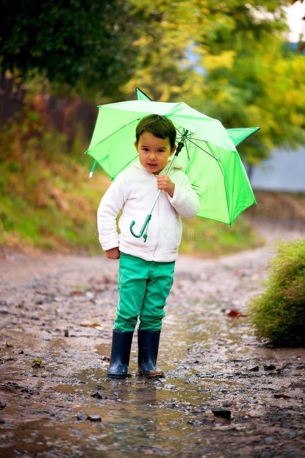 Babymeisje met een paraplu in de regenlooppas door de vulklei stock foto