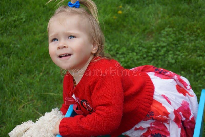 Babymeisje met grote blauwe ogen in rode uitrusting royalty-vrije stock fotografie