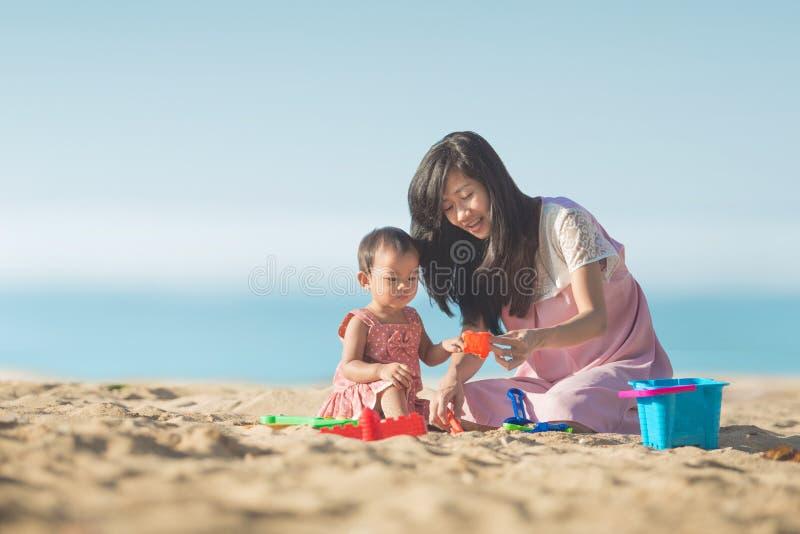 Babymeisje met moeder bij het strandspel met speelgoed op het zand stock afbeelding