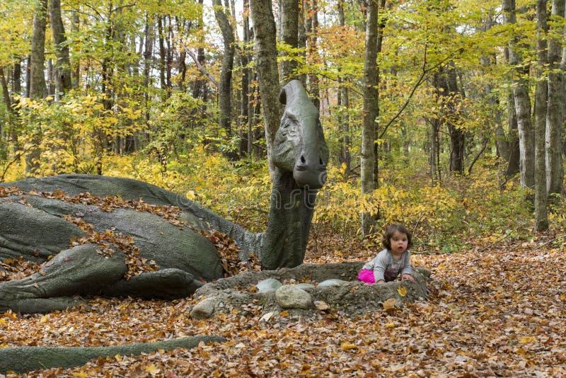 Babymeisje naast hoogtepunt - groottedinosaurus royalty-vrije stock foto's
